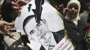 Palestinians hold a poster depicting US President Barack Obama during a protest against his visit in the West Bank city of Nablus