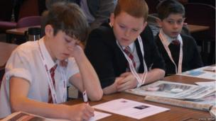 Students study the newspapers at their desks for BBC News School Report