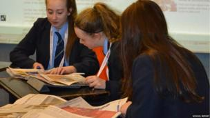 Three students study the newspapers in preparation for News Day 2013