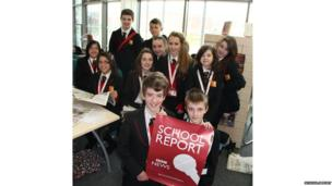 Students pose for the camera with a School Report poster