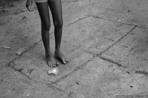 A girl plays hopscotch with a battered plastic glass in a Bangladesh enclave in India.