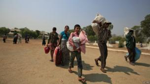 Muslims carry their belongings as they arrive at a stadium amid riots in Meiktila, 22 March 2013
