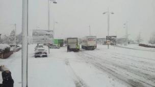 Lorries struggling in the snowy conditions at the A483 B&Q roundabout in Wrexham.