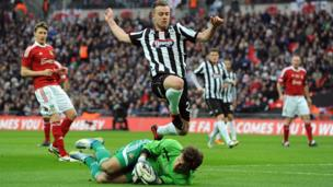 Grimsby Town's Ross Hannah jumps clear of Wrexham goalkeeper Chris Maxwell during the FA Carlsberg Trophy Final at Wembley