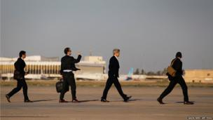 US Secretary of State John Kerry (second from right) walks across the tarmac of Baghdad International Airport