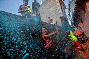 A boy sprays coloured foam during Holi