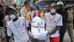 Rescuers from the Tanzania Red Cross carry away a body from the rubble of a collapsed building in Dar es Salaam, Tanzania, 29 March 2013