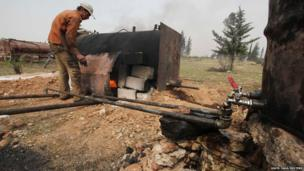 A man works at a makeshift oil refinery site in Aleppo's countryside, Syria
