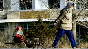 This file photo dated 11 December 2003 shows a North Korean woman pulling her child on a wheel-cart at the North Korean border city of Kaesong.