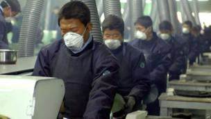 North Koreans work at the factory of Living Art, a kitchenware maker, which became the first South Korean firm to start production in a joint industrial park in the North Korean border city of Kaesong, 15 December 004.