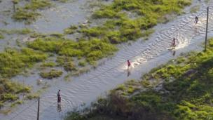 Children on the outskirts of La Plata run through flood waters, 3 April 2013