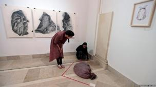 Visitors look at a latex russet-coloured sack designed to feel like human skin at an exhibition in Islamabad