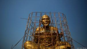 Workers climb scaffolding as they apply final touches to a large religious statue at a Buddhist temple near Amphawa floating market