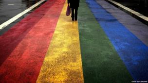 A pedestrian walks across a rainbow pedestrian crossing painted on Sydney's Oxford street,