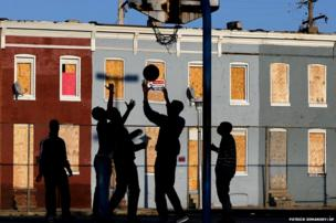 Children play basketball at a park near a blighted row of houses in Baltimore, USA