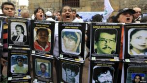 "Protesters hold up banners with the pictures of victims and the slogan ""I neither forgive nor forget, punish the guilty!"""