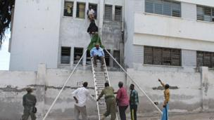 Survivors are helped to escape from a window at Mogadishu's court buildings