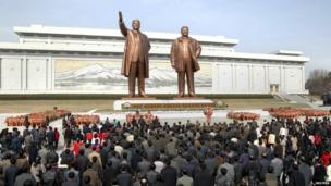 North Korean soldiers, workers and students place flowers before the statues of North Korean founder Kim Il-sung (L) and his son, late leader Kim Jong-il, on the 101st anniversary of Kim Il-sung's birth, at Mansudae in Pyongyang, in this photo distributed by North Korea's official Korean Central News Agency