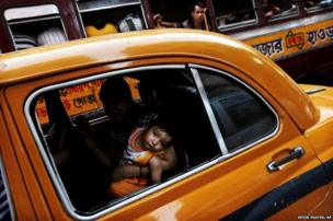 An Indian woman holds her child as they ride in the back of a taxi in Calcutta