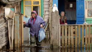 A social worker walks in floodwaters from the Prypyat river