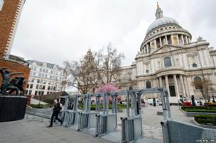 A man walks through temporary security fixtures and barriers installed near to St Paul's Cathedral in central London