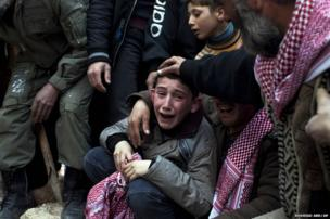A boy named Ahmed mourns his father, Abdulaziz Abu Ahmed Khrer, who was killed by a Syrian army sniper, during his funeral in Idlib, northern Syria, 8 March, 2012