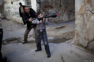 A man teaches Bilal, 11, how to use a toy rocket propelled grenade in Idlib, northern Syria, 4 March 2012