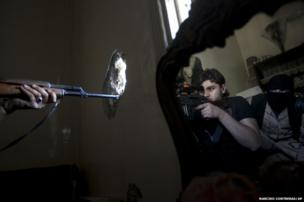 A rebel sniper aims at a Syrian army position in the Jedida district of Aleppo, Syria, 29 October 2012
