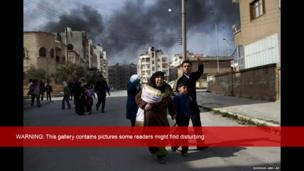 A family escapes from fierce fighting between Free Syrian Army fighters and government troops in Idlib, northern Syria, 10 March 2012