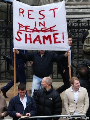 Protestiwr yn dal baner