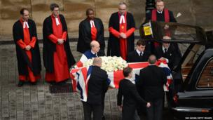 The coffin is transferred to the hearse