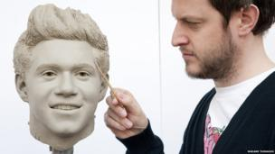 A sculptor works on the clay head of Niall Horan of One Direction.