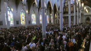 People sitting in church attending interfaith service.