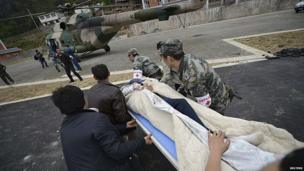 Rescuers rush to carry a victim onto a helicopter after a strong 6.6 magnitude earthquake hit Taiping town of Lushan county, Sichuan province April 20
