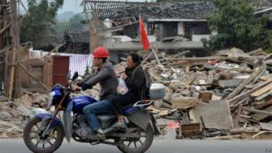 A couple on a motorbike pass flattened houses in Lushan, Sichuan (21 April 2013)