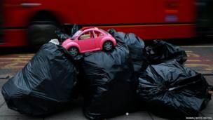 A toy model of a Volkswagen Beetle is seen on top of bags of rubbish