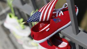 A pair of sports shoes and a US flag hang from the gate of the US embassy in Ottawa, Canada, 22 April