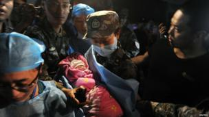 A new-born baby which was born in a relief tent is attended by medical staff after Saturday's earthquake hit Lushan county, Sichuan province in China