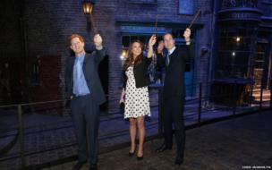 Prince Harry, the Duchess and Duke of Cambridge raise their wands on the set used to depict Diagon Alley in the Harry Potter Films
