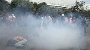 Supporters of a native Indian community living at the Brazilian Indian Museum stand amid tear gas during clashes with military police officers as they protest against the community's eviction in Rio de Janeiro March 22, 2013.