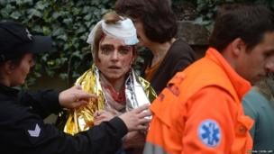 A police woman and paramedic wrap a thermo foil around a woman injured by a powerful gas blast