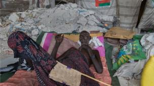 Mohammed Musa reclines on a makeshift bed in the ruins of an abandoned government building in Mogadishu, Somalia