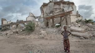 A boy in front of ruined buildings in Mogadishu, Somalia