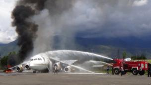 Fire fighters try to extinguish a fire on a BAe 146 cargo plane