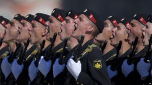 Russian marines stand in line to salute whilst holding guns.