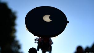 A focused image onto a white background through a telescope shows the moon crossing in front of the sun