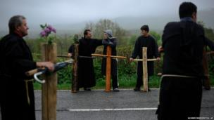 Penitents rest beside their crosses in Spain
