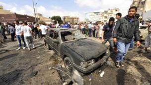 People gather at the scene of a car bomb explosion outside a hospital in Benghazi, 13 May
