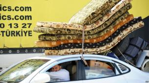 Syrian refugee with mattresses and suitcases tied on top of his car at the Cilvegozu border gate (14 May 2013)