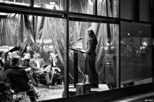 Dominique Renda giving a poetry reading at a bookstore
